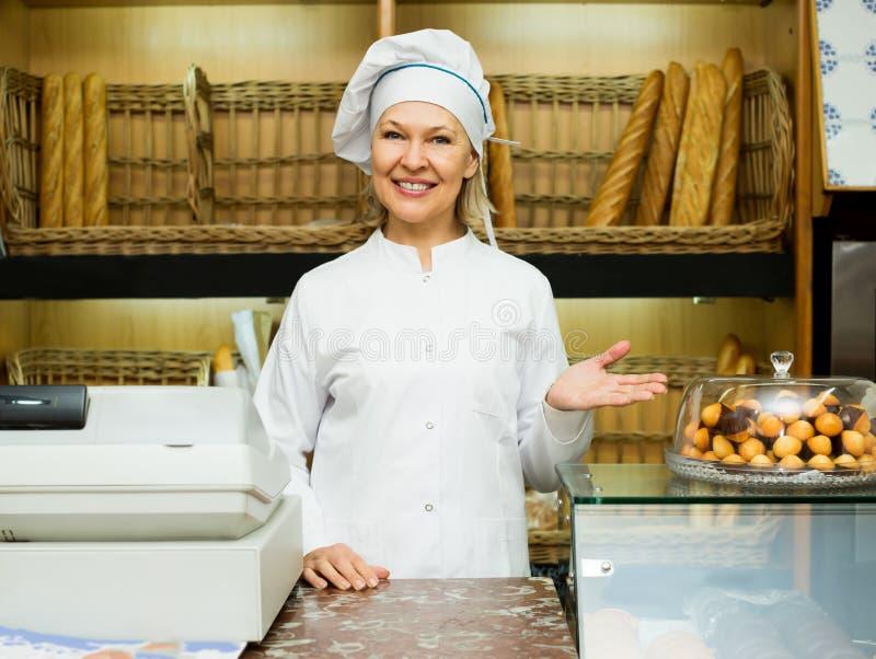 Mogen kvinna som poserar i bageri med bagetter arkivfoto