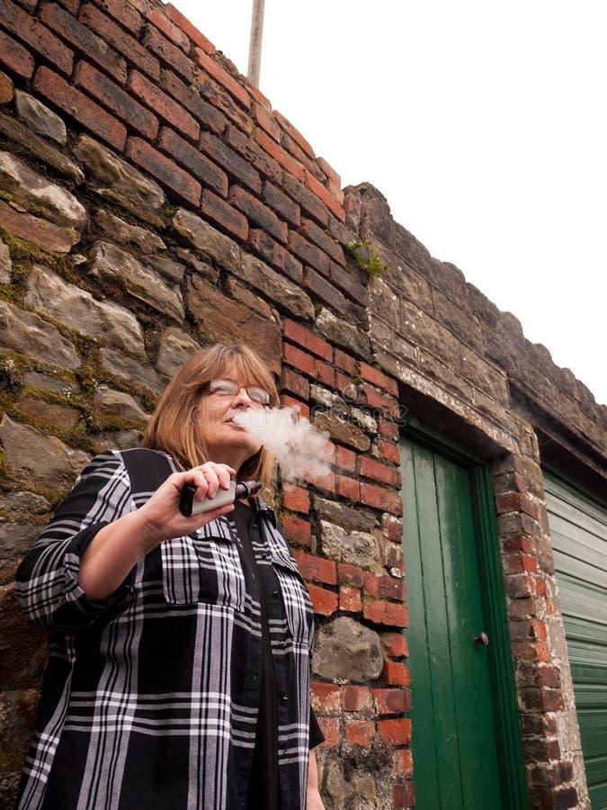 Mogen kvinna som röker en elektronisk cigarett arkivbild