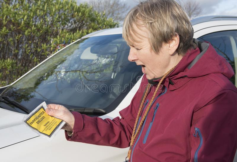 Mogen kvinna som rymmer en parkeringsbiljett royaltyfri fotografi