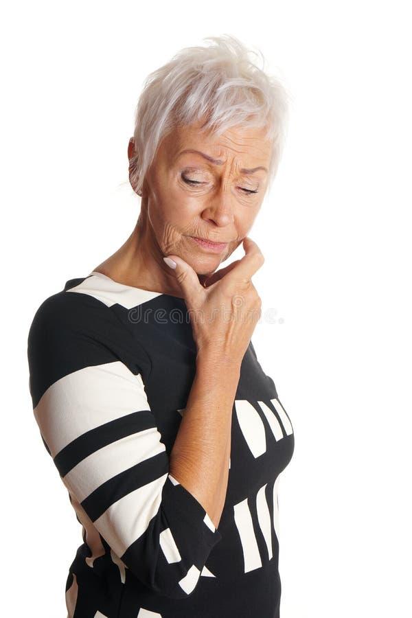 Mogen kvinna som ser besvärad arkivfoto