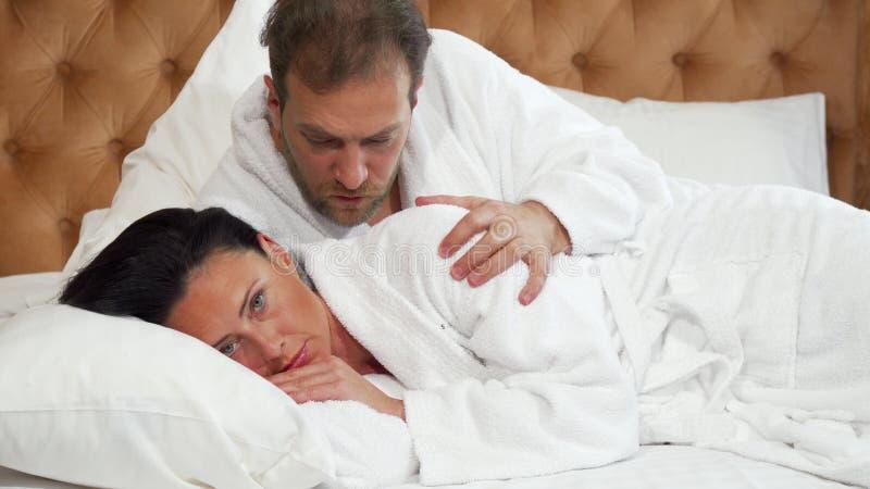 Mogen kvinna som ser dissapointed, hennes försökande samtal för make till henne i säng arkivbilder