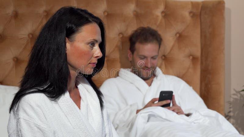 Mogen kvinna som ser olycklig medan hennes make som smsar på den smarta telefonen arkivfoton