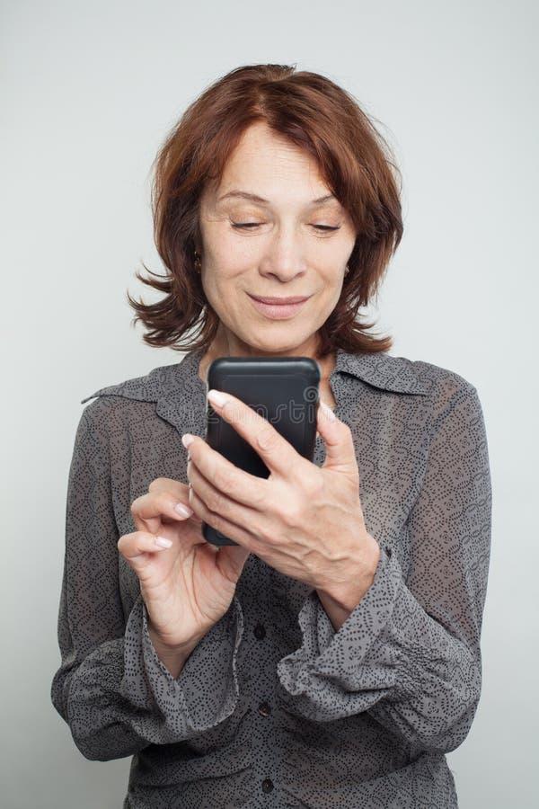 Mogen kvinna som smsar på vit bakgrund royaltyfria foton
