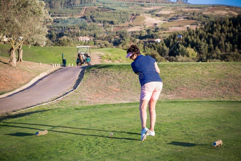 Mogen kvinna som spelar golf royaltyfri bild