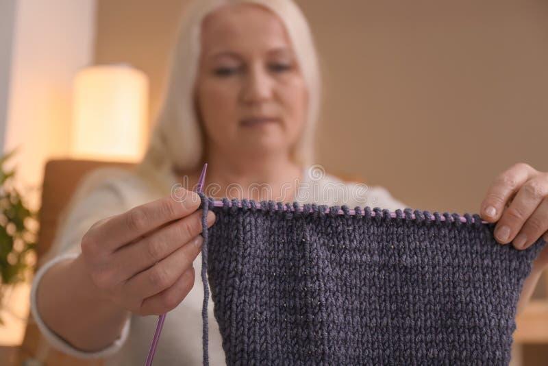 Mogen kvinna som sticker den varma tröjan, closeup arkivbild