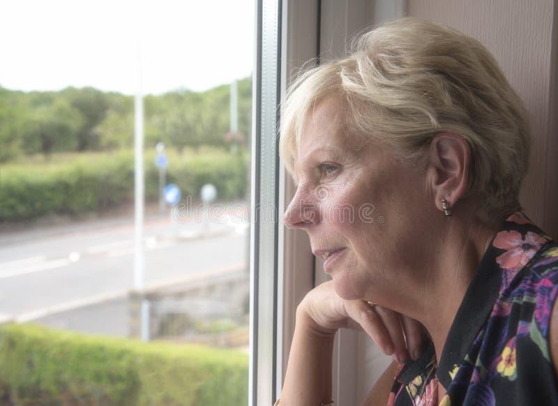 Mogen kvinna som tänker och ser ut ur ett fönster arkivfoton