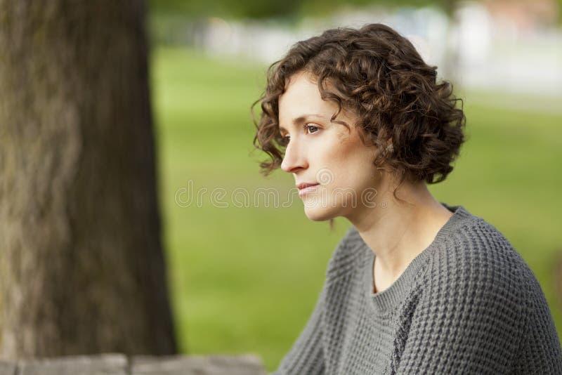 Mogen kvinna som tänker på parkera royaltyfria foton