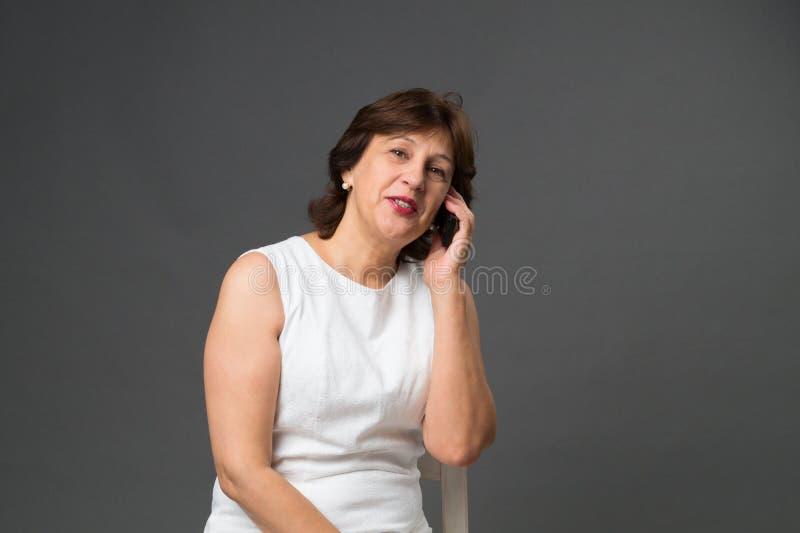 Mogen kvinna som talar på telefonen, en mörk bakgrund arkivbilder