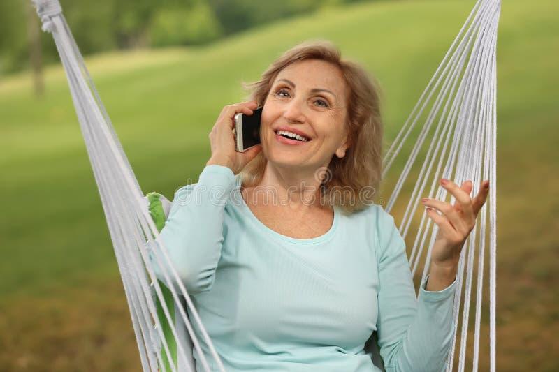 Mogen kvinna som talar vid mobiltelefonen, medan vila utomhus arkivfoto