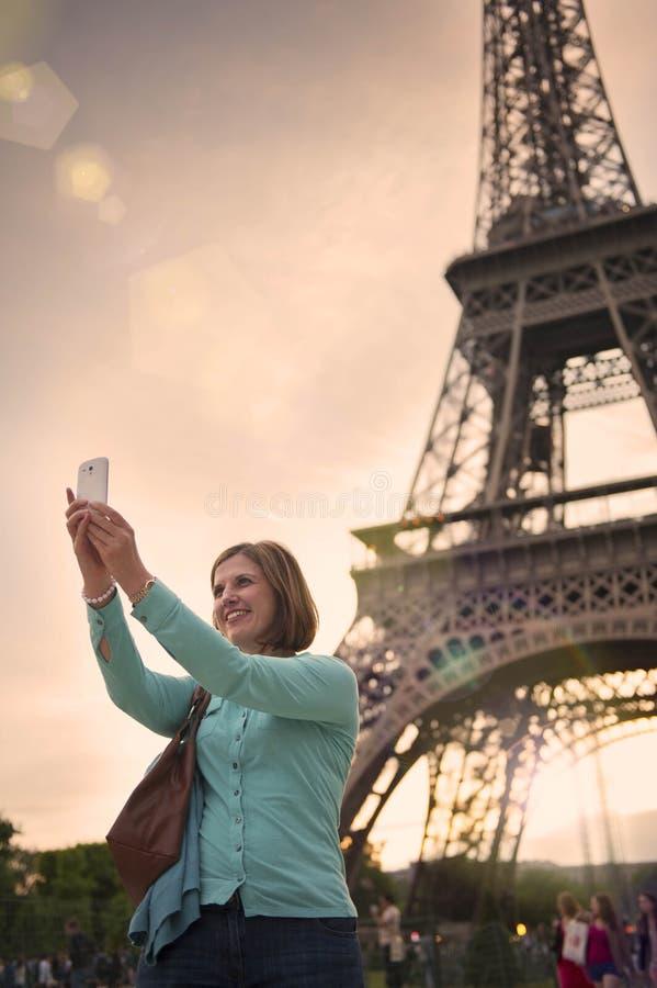 Mogen kvinna som tar en selfie med Eiffeltorn paris royaltyfri fotografi