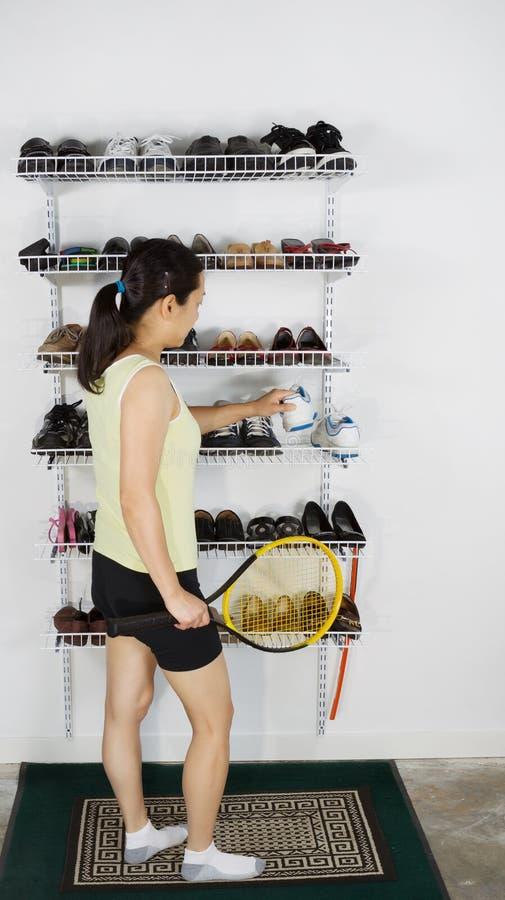 Mogen kvinna som tar skor av kuggen för tennisperiod arkivbild