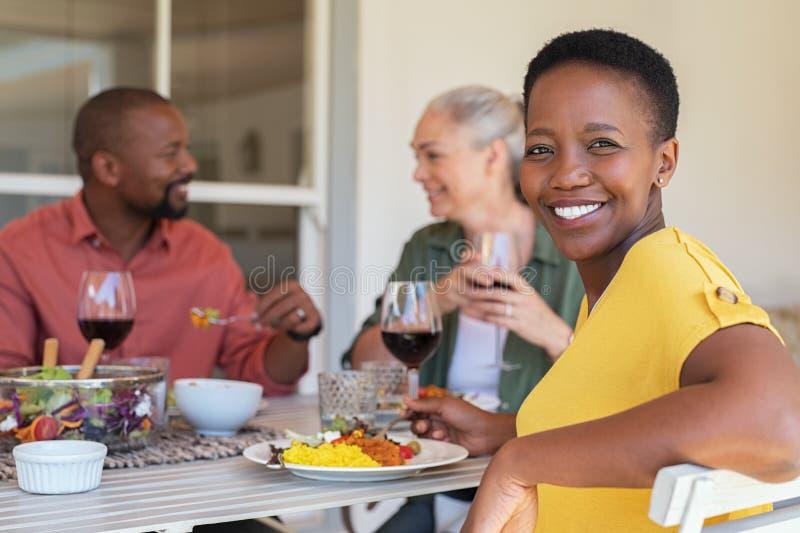 Mogen kvinna som tycker om lunch med v?nner royaltyfria foton
