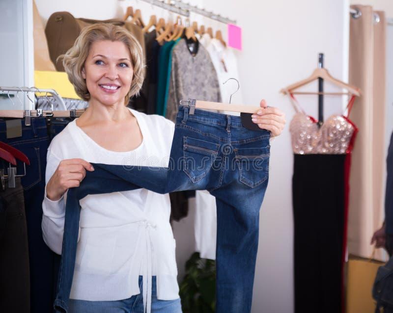 Mogen kvinna som väljer jeans i shoppa royaltyfria foton