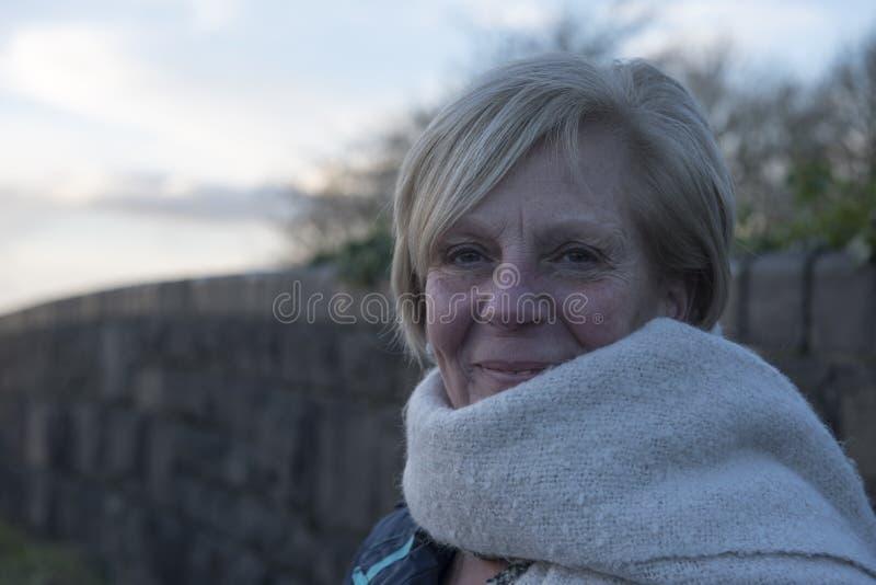 Mogen kvinna utomhus i vintern som bär en halsduk fotografering för bildbyråer