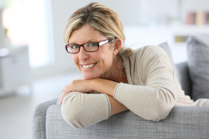 Mogen kvinnabenägenhet på soffan fotografering för bildbyråer