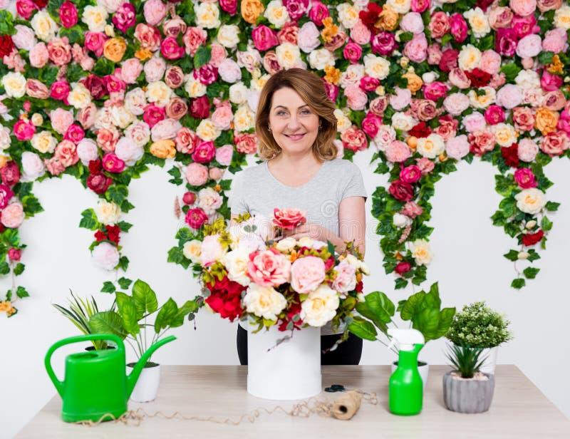 Mogen kvinnablomsterhandlare eller trädgårdsmästare som arbetar i blomsterhandel fotografering för bildbyråer