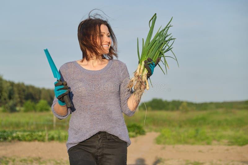 Mogen kvinnabonde som går till och med trädgården med den gröna nya gräslöklöken arkivbild