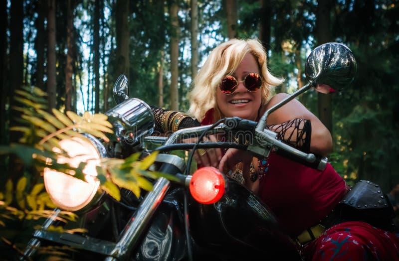 Mogen kvinnacyklist på en motorcykel arkivbild