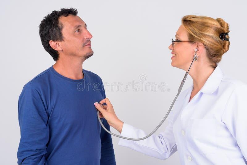Mogen kvinnadoktor som kontrollerar den mogna manpatienten mot vit bakgrund arkivbild