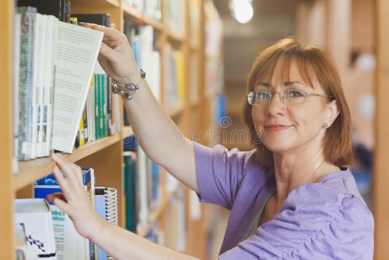 Mogen kvinnlig bibliotekarie som tar en bok av en hylla arkivbilder