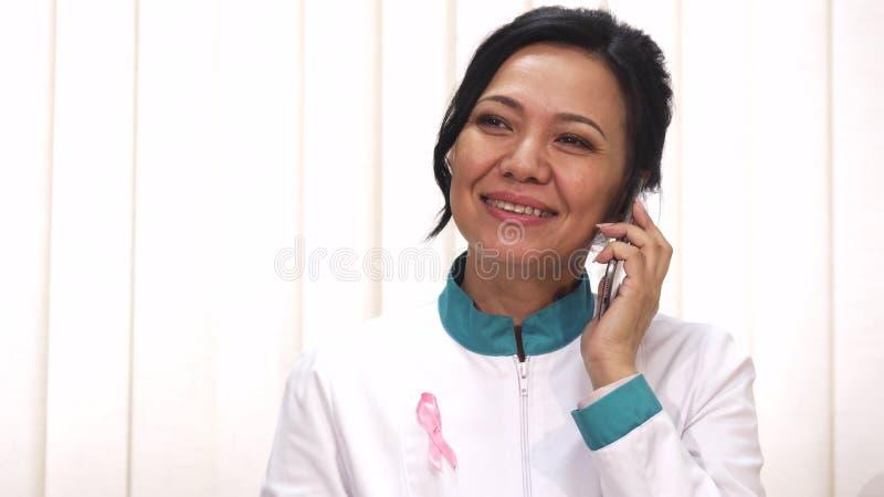 Mogen kvinnlig doktor för härlig asiat som talar på telefonen som joyfully ler arkivfoton