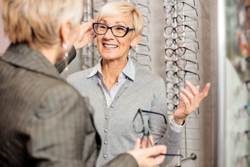 Mogen kvinnlig säljare som hjälper le den höga kvinnan för att välja receptexponeringsglas i optikerlager royaltyfri foto