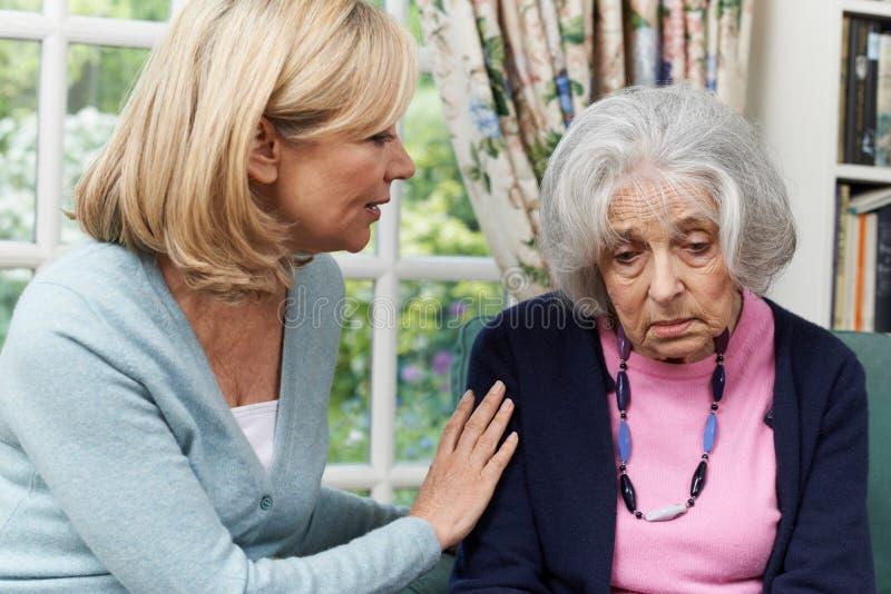 Mogen kvinnlig vän som tröstar den olyckliga höga kvinnan royaltyfria foton