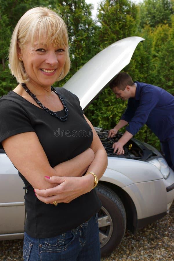 Mogen kvinnligbilist som har henne reparation bil arkivfoto