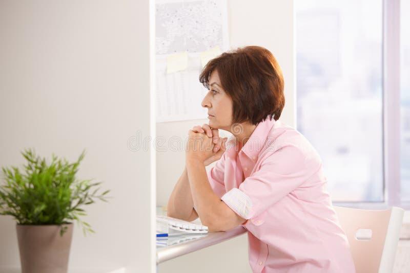 Mogen kvinnligkontorsarbetare som tänker på skrivbordet royaltyfri fotografi