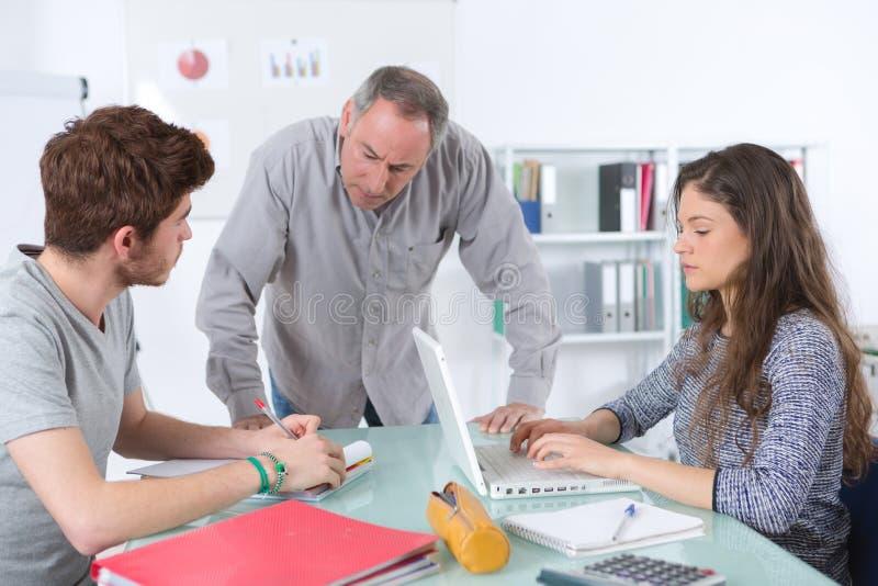 Mogen lärare och tonåriga studenter i klassrum arkivbilder