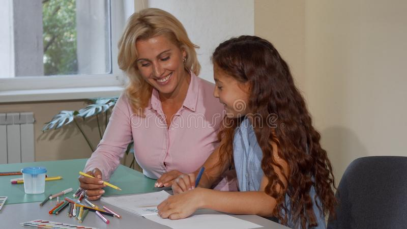 Mogen lärarinna som tycker om att arbeta med hennes lilla student på skola arkivbild