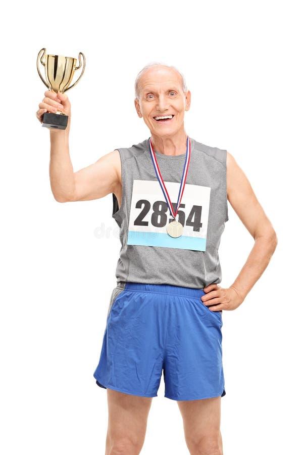 Mogen löpare som rymmer en trofé och firar seger arkivfoton
