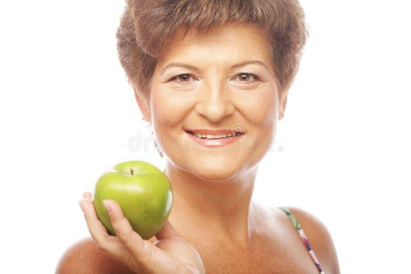 Mogen le kvinna med det gröna äpplet fotografering för bildbyråer