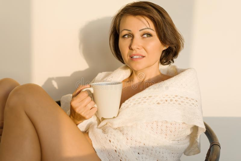 Mogen le kvinna som hemma sitter i stol i woolen stucken filt med koppen av den varma drinken, höstvinterstil royaltyfri foto