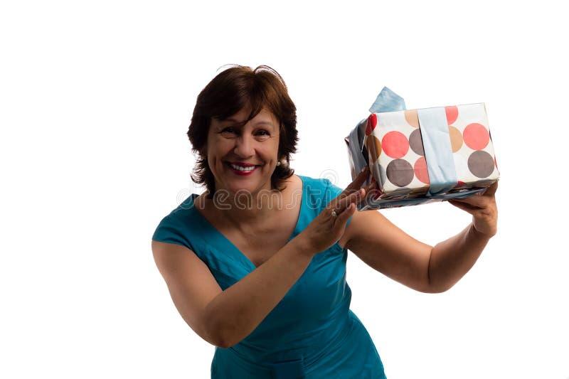 Mogen lycklig attraktiv kvinna med gåvan på vit bakgrund royaltyfria foton