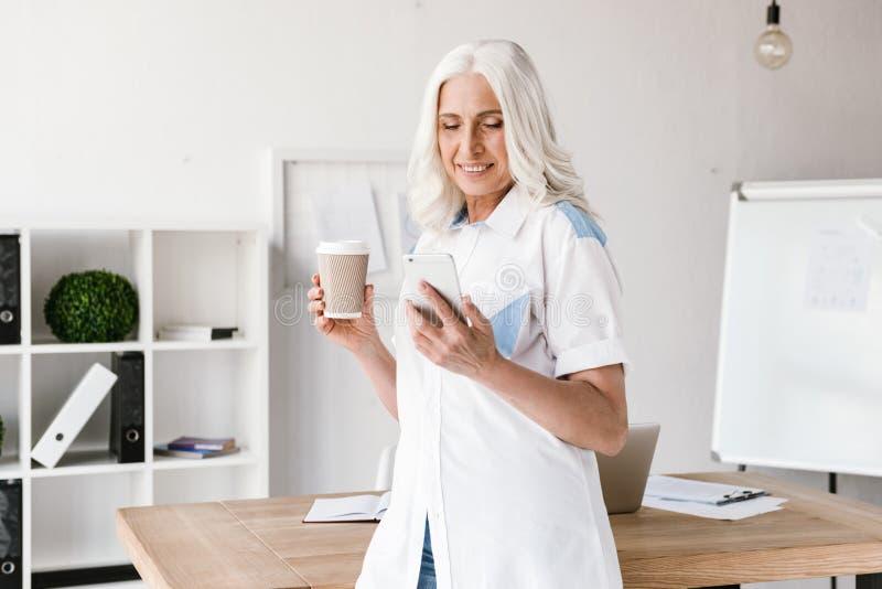 Mogen lycklig kvinna som dricker kaffe genom att använda mobiltelefonen arkivbilder