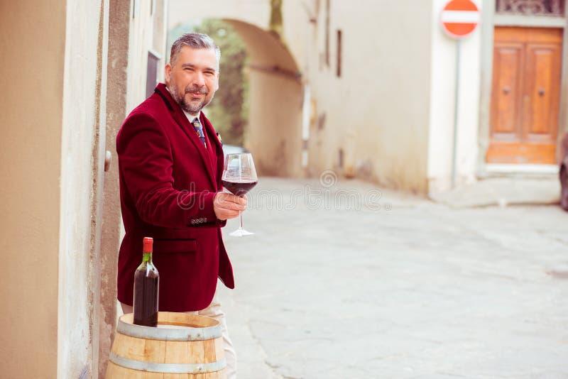 Mogen lycklig le man med exponeringsglas av rött vin utomhus i gammal italiensk by royaltyfria bilder