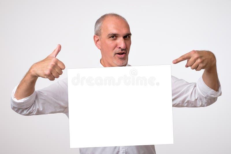 Mogen man för latinamerikan som pekar på copyspace Positiv lyckad manlig chef i vitt göra en gest för skjorta royaltyfria foton