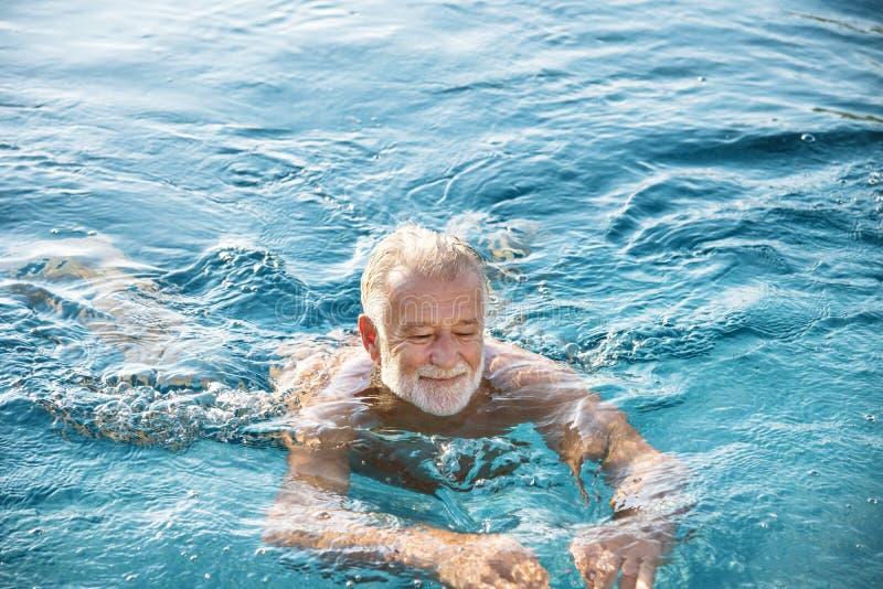 Mogen man i en simbassäng royaltyfria bilder