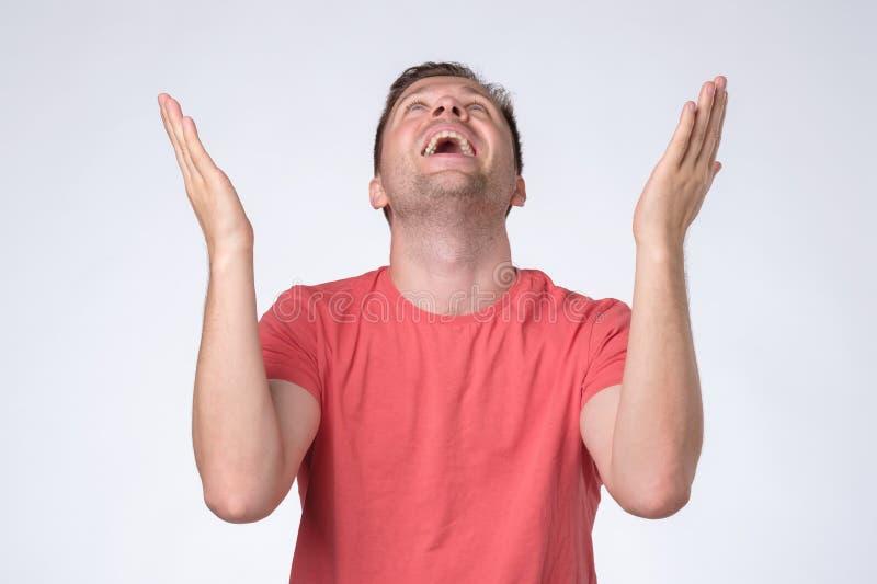 Mogen man i röd t-skjorta som frågar från himmel som lyfter hans hand royaltyfri fotografi