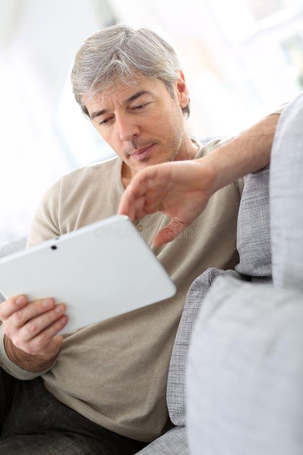Mogen man i soffan som websurfing arkivfoto