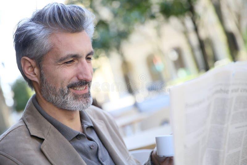 Mogen man i stad som dricker kaffe och den läs- tidningen arkivbild