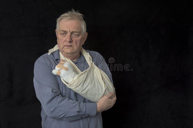 Mogen man med den sårade armen i en rem royaltyfri fotografi