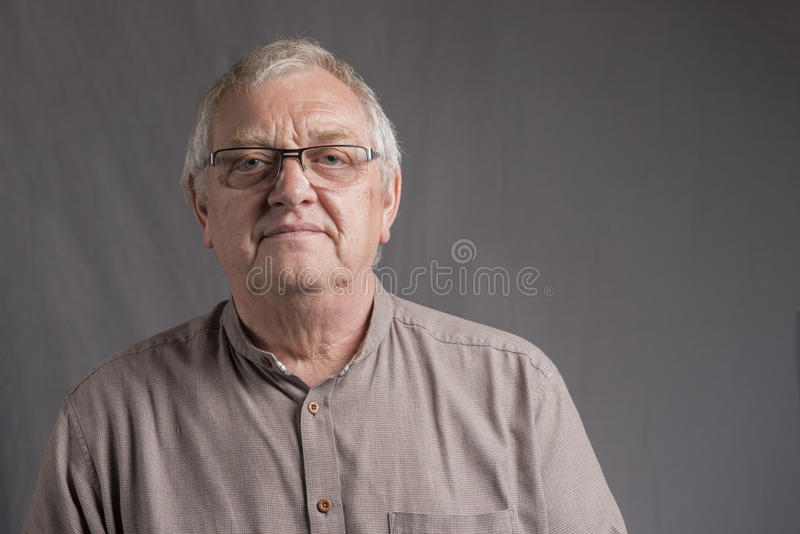 Mogen man med gråa hår och exponeringsglas arkivfoton