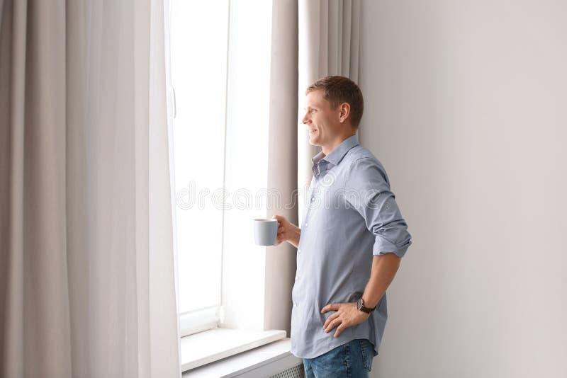 Mogen man med koppen av drinken nära fönster med öppna gardiner hemma fotografering för bildbyråer