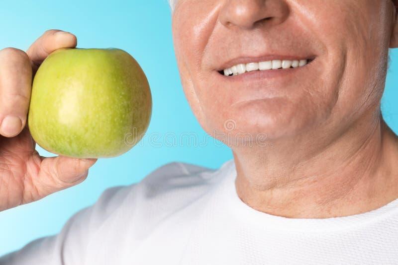 Mogen man med sunda tänder som rymmer äpplet på färgbakgrund arkivfoto