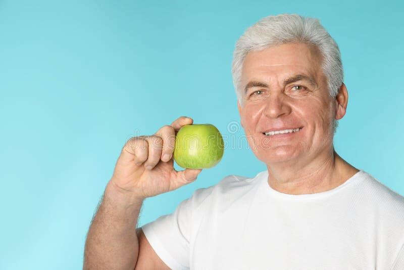 Mogen man med sunda tänder som rymmer äpplet arkivfoto