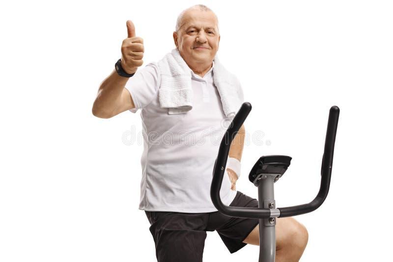 Mogen man på en motionscykel som visar upp tummar arkivbild