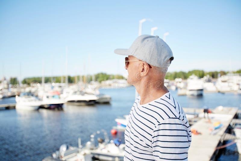Mogen man på semester i yachtklubba royaltyfri fotografi