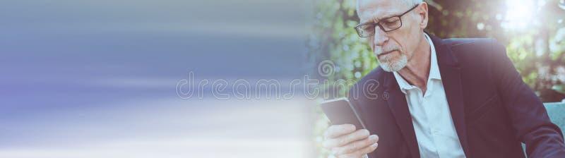 Mogen man som använder hans mobiltelefon panorama- baner royaltyfri bild